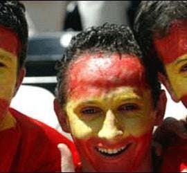 Hinchas de fútbol con la bandera española pintada en la cara.