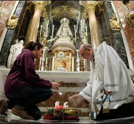 Osoro y una joven encienden una vela