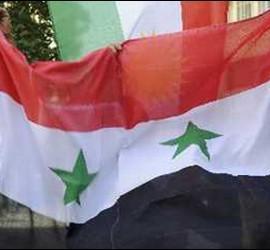Jóvenes se manifiestan en Siria junto a la bandera del país.