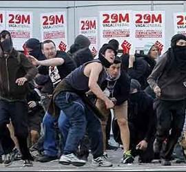 Manifestantes antisistema atacando a la policía durante la huelga general.