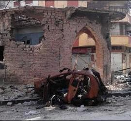 <p>Fotografía hecha pública por los Comités de Coordinación Locales (LCC) en Siria donde se muestra un coche y unos edificios dañados en el barrio de Jorat Al-Shayyah, en Homs, Siria. EFE</p>