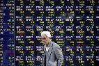 Un hombre camina frente a un tablero electrónico que indica los resultados de la Bolsa de Tokio (Japón).