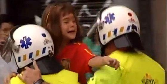 Un sanitario lleva en brazos a una niña con la camiseta de España, a cuya familia intentaba agredir un grupo de independentistas catalanes.