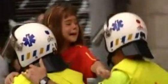 Un sanitario lleva en brazos a una niña con los colores de España, a cuya familia increpaba e intentaba agredir un grupo de independentistas catalanes.