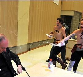 Activistas rocían a Léonard con agua bendita