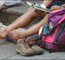 Los pies, las botas y la mochila del peregrino en el Camino de Santiago.