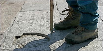 La concha, el bordón, las botas y los pies de un peregrino en el Camino de Santiago.