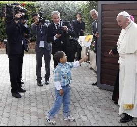 Un niñlo ofrece una banderita al papa en Asís