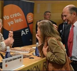 Isabel firma el libro en presencia de Rodríguez Braun