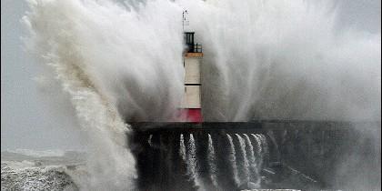 Las olas del mar estrellándose contra un faro.
