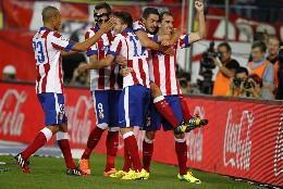 Los jugadores del Atlético de Madrid, rodean a Mandzukic, con máscara.