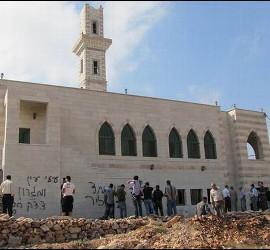 Musulmanes palestinos contemplan las pintadas en la fachada del templo