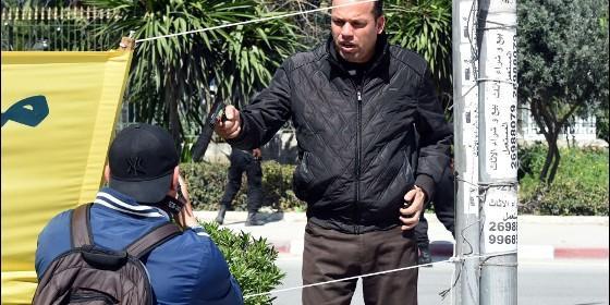 Un policía tunecino apunta con un arma a un fotógrafo que se encuentra en la zona del Museo del Bardo, donde se han atrincherado los yihadistas islámicos.