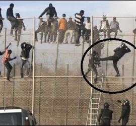 Un guardia civil forcejea con los inmigrantes ilegales encarmados a la valla de Melilla.