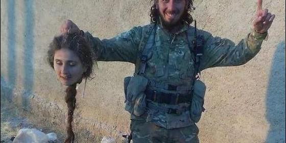 Un miliciano islámicos exhibe la cabeza decapitada de una mujer.