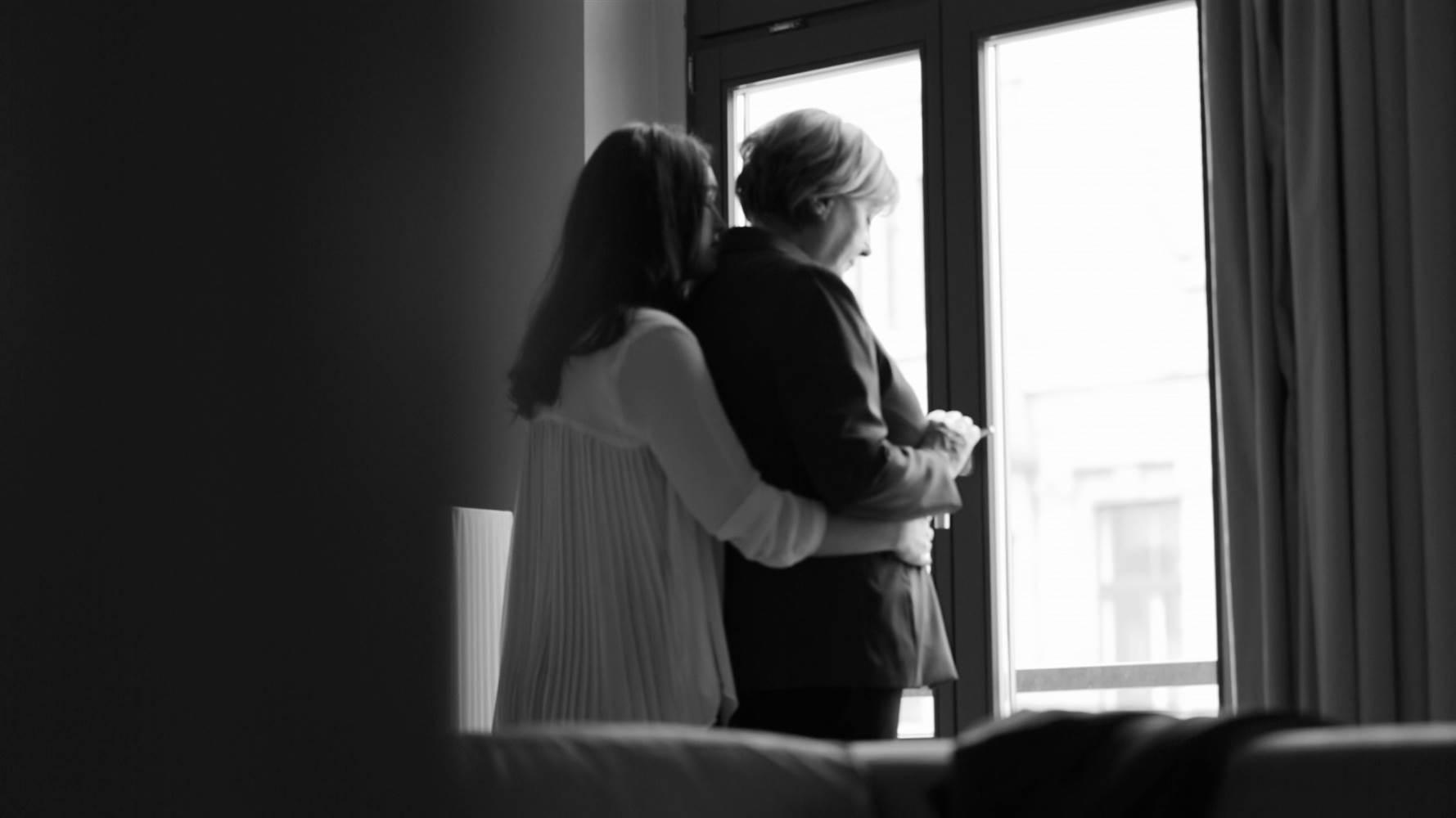 En Ese Momento Aparece Otra Mujer Mas Joven Y En Camison Que La Abraza Tiernamente Por La Espalda Y Le Da Un Beso En El Cuello A Lo Que Ella Responde