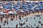 Vacaciones, playa, sombrilla, toalla, turista, tumbona y mar.