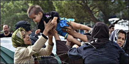 Una inmigrante ilegal pasa a su niño por encima de la alambrada que separa Serbia de Hungría.