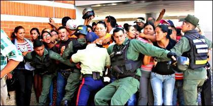 La GNB y de la Brigada Antimotín chavista intenta impedir que la multitud irrumpa en el supermercado en Venezuela..