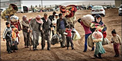 Refugiados sirios cruzan la frontera con Turquía.