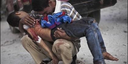Un padre sostiene el cadáver de su hijo muerto en un tiroteo en Siria.