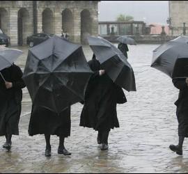 Un grupo de monjas se protege de la lluvia