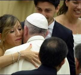 Francisco abraza a unos novios