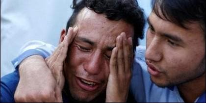 Dos afganos de la minoría hazara, lloran tras el atentado del ISIS.