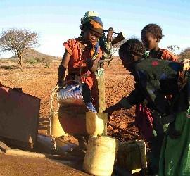 Niñas cogiendo agua de un pozo