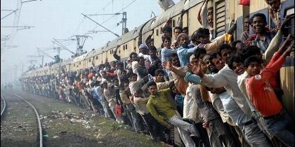 Un atestado tren en la India, con pasajeros colgados de las ventanillaas y en el techo.