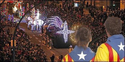 La cabalgata de los Reyes Magos en Barcelona y dos jóvenes con la estelada.