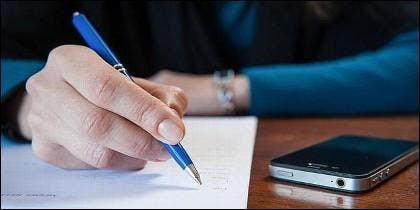 Bolígrafo, escritura manual y teléfono móvil.