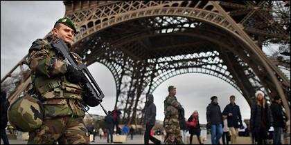 Un militar de patrulla bajo la Torre Eiffel.