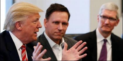 El presidente Trump charla en presencia de Peter Thiel (centro), miembro del consejo de Facebook, y Tim Cook, consejero delegado de Apple.