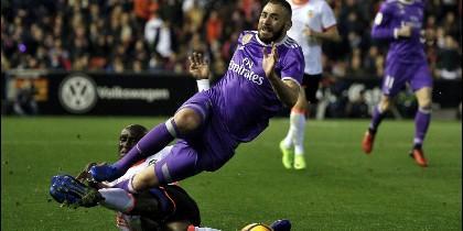 El delantero francés del Real Madrid Karim Benzema (d) es entrado en falta por el defensa francés del Valencia Eliaquim Mangala (i).