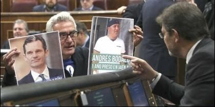 Cañamero (PODEMOS), con las fotos de Bódalo y Urdangarín, ante el escaño del ministro Catalá, en el Congreso de los Diputados.