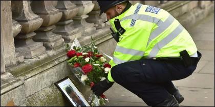 Un policía británico depositando flores junto a la foto de su compañero asesinado