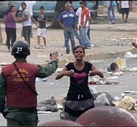 Un policía chavista apunta con su pistola a una mujer que protesta contra la carestía de alimentos en Venezuela.