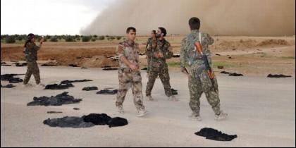 Rebeldes sirios miran niqabs abandonados en Raqqa.