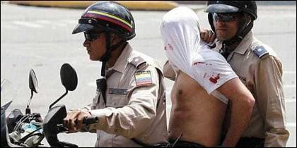 Sicarios chavistas del tirano Maduro llevan a un opositor detenido.
