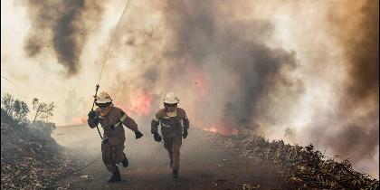 Dos bomberos se alejan del incendio en Portugal.
