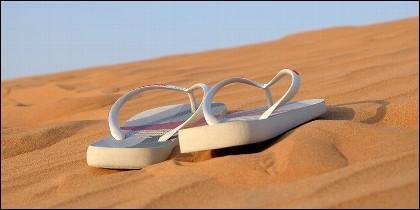 Playa, arena, turista, viaje, chanclas y vacaciones.