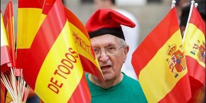 Un manifestante catalán, a favor de la Constitución, luciendo la barretina y la bandera española.
