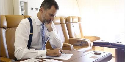 Felipe VI revisa unos textos durante un vuelo