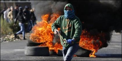 Manifestantes palestinos lanzando bolas de hierro contra los soldados israelíes.