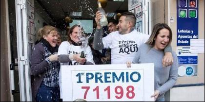 Catalina Durán (2i), de la administración de lotería 'La Biznaga', de Málaga, celebra junto a sus clientes.