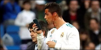 Cristiano Ronaldo mira en el móvil del médico del Real Madrid la herida que tiene en la cara.