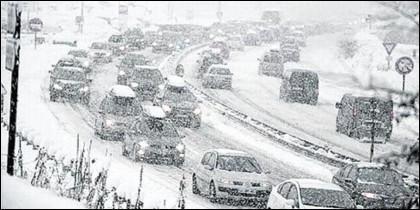 Tráfico complicado y coches atrapados en la carretera, por el temporal de hielo y nieve.