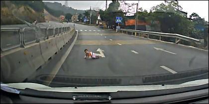El bebé traviesa gateando la carretera, en medio del tráfico.