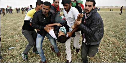 Militantes de Hamas trasportan a un palestino muerto por una bala israelí en la frontera de Gaza.